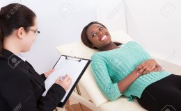 26835539-Happy-female-patient-talking-to-psychologist-while-lying-on-bed-in-clinic-Stock-Photo